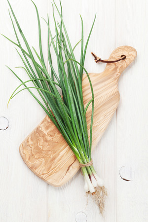 Fresh garden spring onion on cutting board. Top view