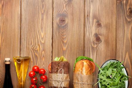 サラダ、ハム、チーズ、トマト、サラダ、木製のテーブルの上のスパイスと 2 つのサンドイッチ。コピー スペース平面図