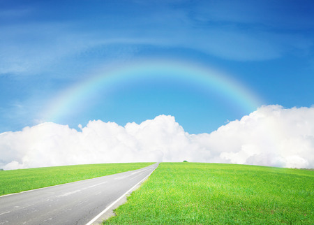 Summer landscape with endless asphalt road through the green field and blue sky with clouds and rainbow Stock Photo
