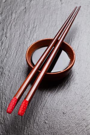 sauce bowl: Japanese sushi chopsticks over soy sauce bowl on black stone background