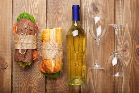 bread and wine: Dos bocadillos y vino blanco en mesa de madera. Vista superior
