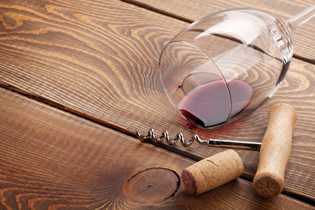 Wine glass, cork and corkscrew over wooden table with copy space Foto de archivo