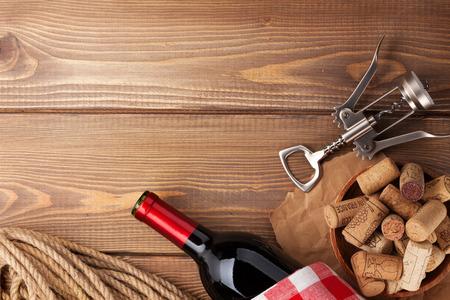 bouteille de vin: Bouteille de vin rouge, bouchons et tire-bouchon sur bois fond de tableau. Vue de dessus avec copie espace