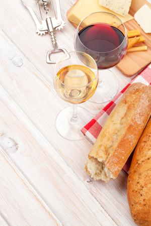queso blanco: Blanco y rojo vino, el queso y el pan en blanco de madera fondo de la tabla. Vista superior con espacio de copia