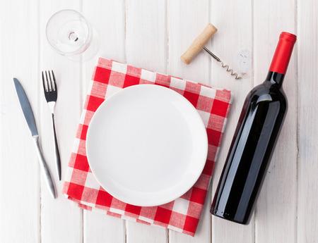 copa de vino: Mesa con plato vacío, copa de vino y una botella de vino tinto. Vista superior sobre fondo rústico mesa de madera
