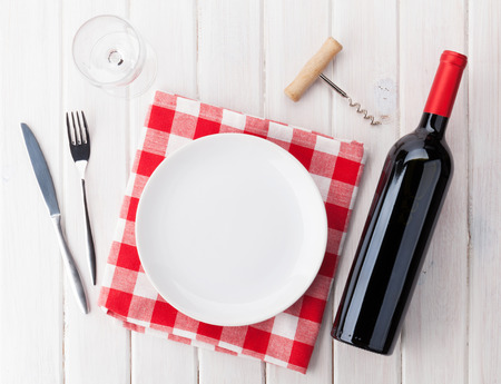 setting: Table setting with empty plate, wine glass and red wine bottle. Top view over rustic wooden table background