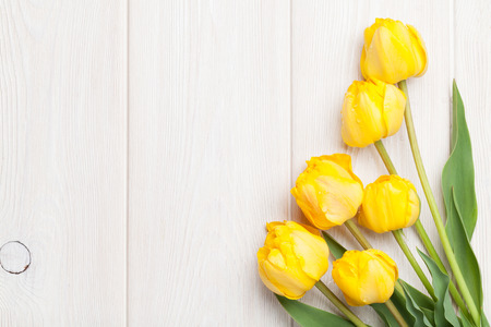spring background: Yellow tulips over wooden table background with copy space