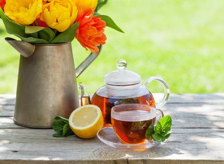 breakfast garden: Breakfast tea on garden table and colorful tulips bouquet Stock Photo