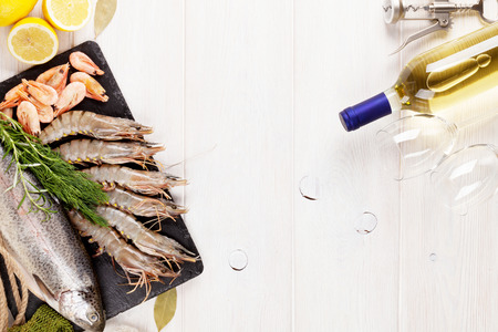 food and wine: Fresh raw sea food with spices and white wine on wooden table background. Top view with copy space Stock Photo