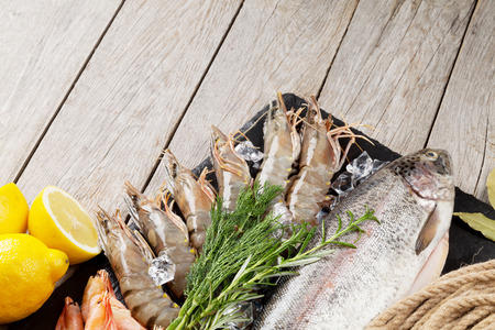 rainbow fish: Fresh raw sea food with spices on stone plate over wooden table background. Top view