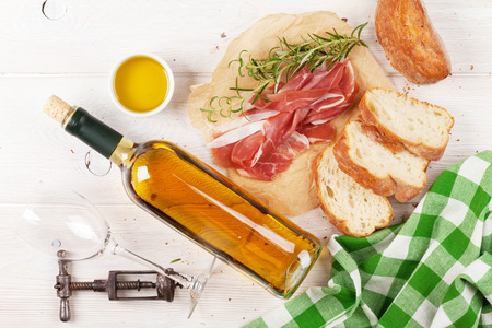 Prosciutto, wine, ciabatta, parmesan and olive oil on wooden table. Top view 版權商用圖片 - 42148417