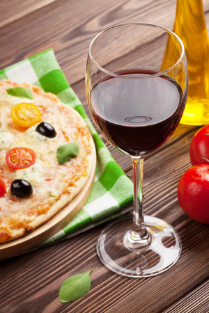 food and wine: Glass of red wine and italian pizza with cheese, tomatoes, olives and basil