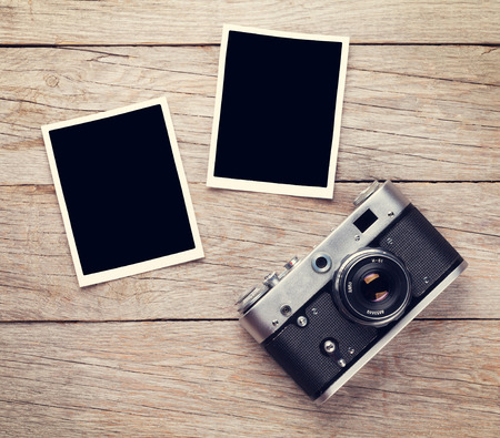 Vintage film camera and two blank photo frames on wooden table. Top view Stok Fotoğraf
