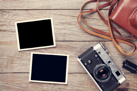 aged wood: Vintage film camera and two blank photo frames on wooden table. Top view Stock Photo
