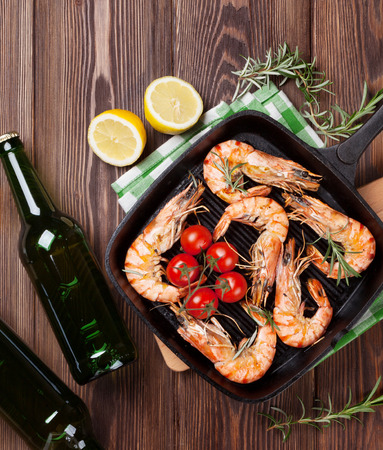prepared shrimp: Grilled shrimps on frying pan and beer on wooden table. Top view