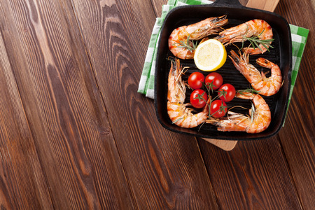 prawn: Grilled shrimps on frying pan on wooden table. Top view with copy space