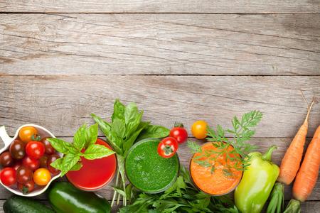 fondo: Batido de verduras frescas en la mesa de madera. Tomate, pepino, zanahoria. Vista superior con espacio de copia