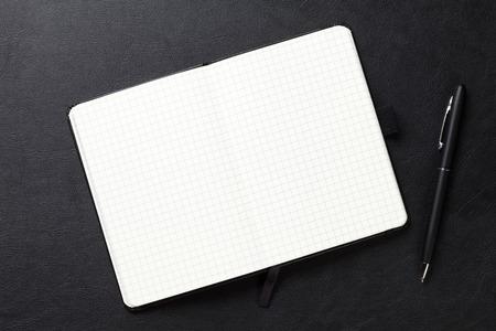 nota de papel: Bloc de notas y pluma en el escritorio de cuero de la oficina. Vista superior con espacio de copia