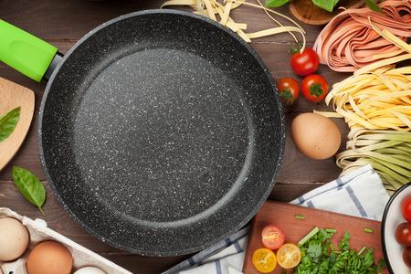 cooking: Ingredientes para cocinar Pasta y utensilios de mesa de madera. Vista superior con el sartén vacía para copiar el espacio