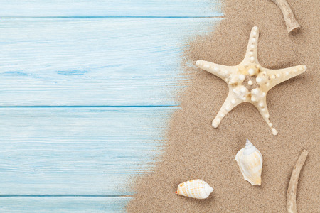 view on sea: Sea sand with starfish and shells on wooden table. Top view with copy space