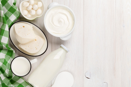 green top: Dairy products on wooden table. Sour cream, milk, cheese, yogurt and butter. Top view with copy space