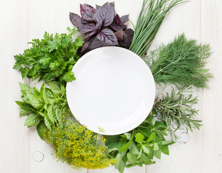 empty: Fresh garden herbs and empty plate on wooden table. Top view with copy space