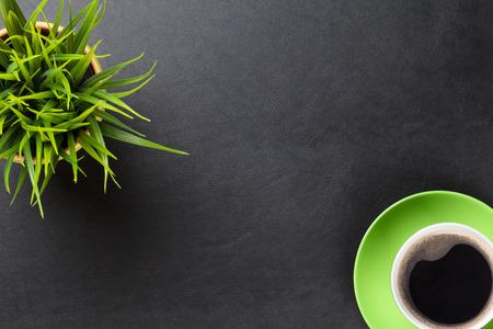 オフィス革デスク テーブル花とコーヒーのカップを持つ。コピー スペース平面図