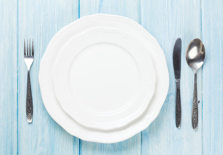 Empty plate and silverware over wooden table background. View from above with copy space Archivio Fotografico