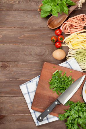 cuisine: Pasta cooking ingredients and utensils on wooden table. Top view with copy space Stock Photo