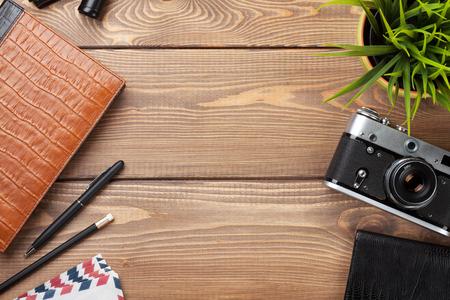 wood table: Mesa Escritorio de oficina con cámara, suministros y flor. Vista superior con espacio de copia Foto de archivo