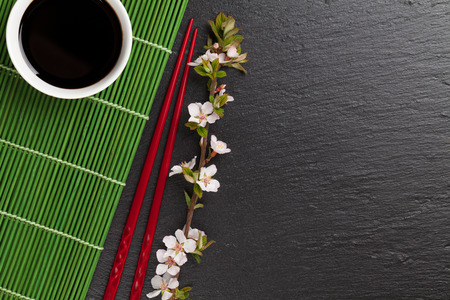black stone: Japanese sushi chopsticks, soy sauce bowl and sakura blossom on black stone background. Top view with copy space Stock Photo