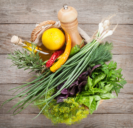 fruits in a basket: Fresh garden herbs and spices on wooden table