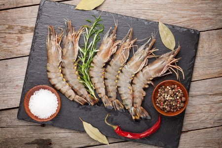 Fresh raw tiger prawns and spices on  black stone plate over wooden table