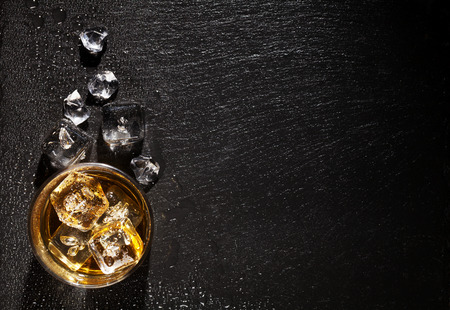 whiskey glass: Glass of whiskey with ice on black stone table. Top view with copy space