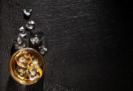 tomando alcohol: Vidrio de whisky con hielo en mesa de piedra negro. Vista superior con espacio de copia