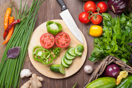 cutting boards: Fresh farmers garden vegetables cooking on wooden table. Top view Stock Photo