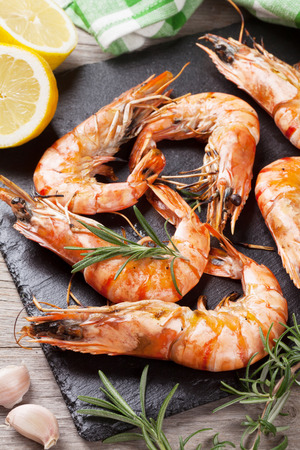 Grilled shrimps on stone plate over wooden table