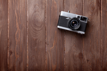 Vintage film camera on wooden table. Top view with copy space