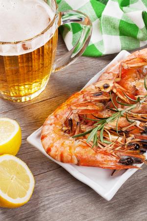 plato de pescado: Beer mug and grilled shrimps on wooden table