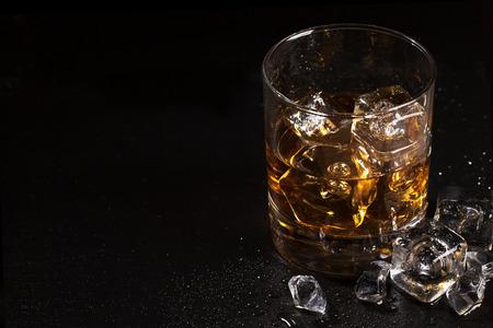 コピー スペースを持つ黒の石のテーブル上の氷とウイスキーのガラス