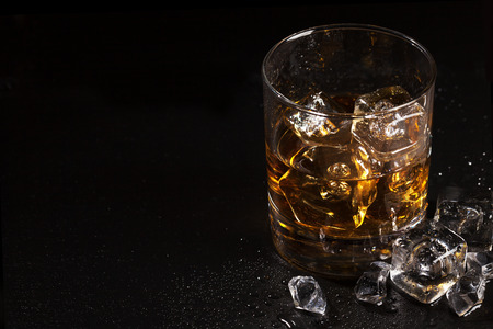 Glass of whiskey with ice on black stone table with copy space