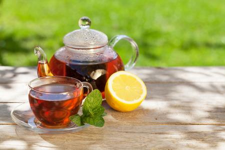 日当たりの良い庭のテーブルで朝食の茶 写真素材