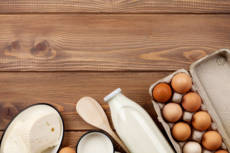 leche y derivados: Productos lácteos en la mesa de madera. Leche, queso y huevos. Vista superior con espacio de copia