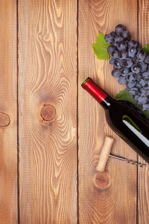 glass table: Red wine bottle and bunch of red grapes on wooden table background with copy space