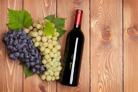 bouteille de vin: Bouteille de vin rouge et grappe de raisins sur table en bois fond Banque d'images