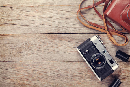 Vintage film camera with case on wooden table. Top view with copy space. Toned Stock Photo