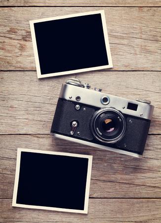 ビンテージ フィルム カメラと木製のテーブルに 2 つの空白のフォト フレーム。トップ ビュー