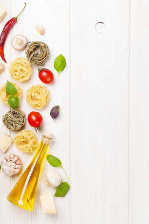 Italian food cooking ingredients. Pasta, tomatoes, basil. Top view with copy space
