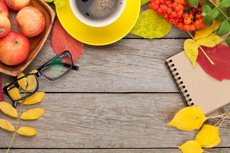 papel de notas: Hojas de oto�o, las manzanas, la taza de caf� y el bloc de notas sobre fondo de madera con espacio de copia