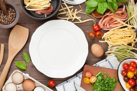 Pasta koken ingrediënten en gebruiksvoorwerpen op houten tafel. Bovenaanzicht met lege plaat voor kopie ruimte Stockfoto
